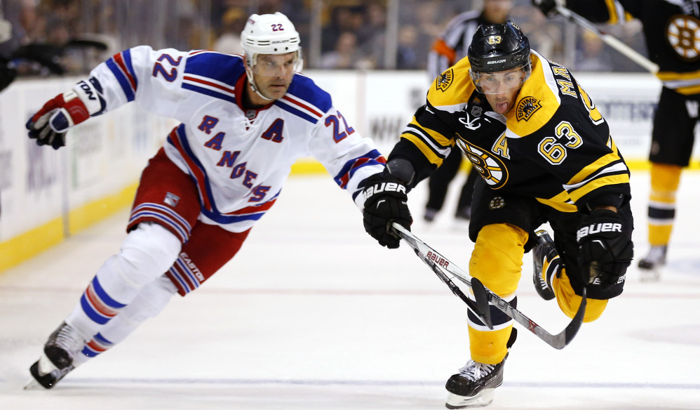 Brad Marchand of the Bruins, right, chases a loose puck with New York's Dan Boyle in Thursday night's exhibition game at Boston. The Bruins rallied for a 4-3 shootout win.