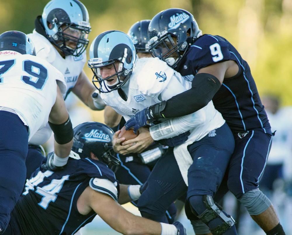 Rhode Island quarterback Paul Mroz feels the pressure from Maine's Trevor Bates, right, and other defenders during the Black Bears' 27-17 win over the Rams on Saturday in Orono.