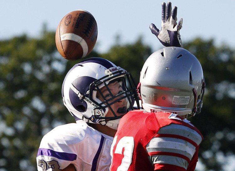 Rob Dacey, left, of Deering breaks up a pass intended for Spencer Houlette of South Portland on the final play of the first half Saturday. The ball bounced off his helmet and was intercepted by teammate Pat Viola. Deering won, 27-14.