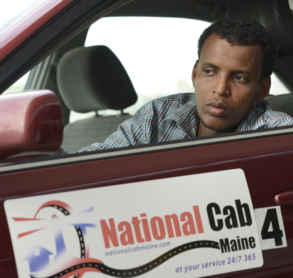 Cab driver Ahmed Issack, waiting for a fare at the Portland jetport, says Uber and Lyft drivers should have to go through the same permitting process that he does.