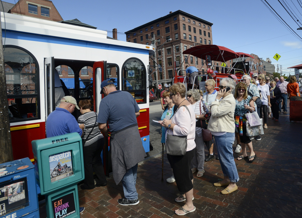 A line forms for the trolley Monday on Commercial Street in Portland. Busier Septembers have changed the operations of businesses that used to shut down right after Labor Day.