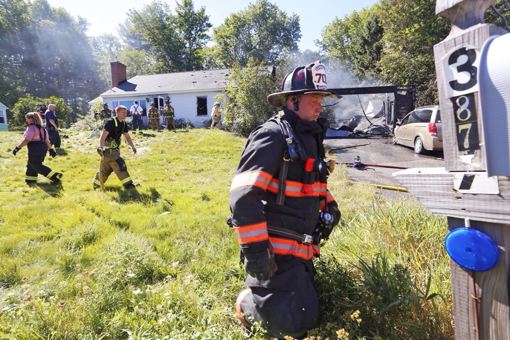Firefighters work at the scene of a house fire Wednesday that started in the garage at 387 South St. in Biddeford. One person was home and safely out of the house when emergency responders arrived, according to acting Fire Chief Scott Gagne. Derek Davis/Staff Photographer