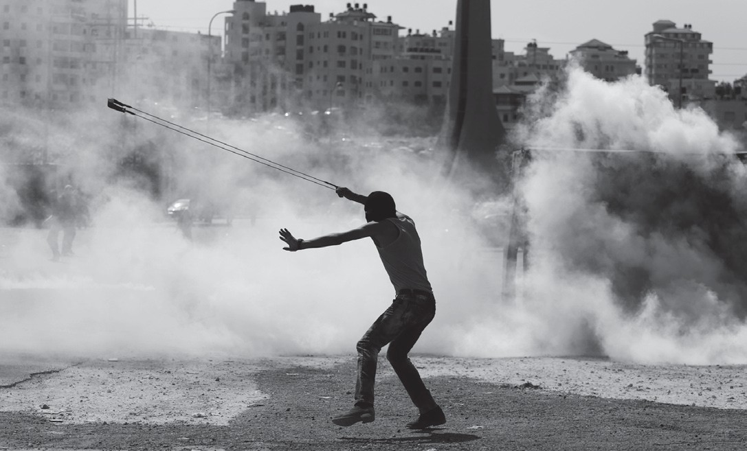 A Palestinian demonstrator uses a slingshot during clashes following a demonstration in the West Bank city of Ramallah on Monday.