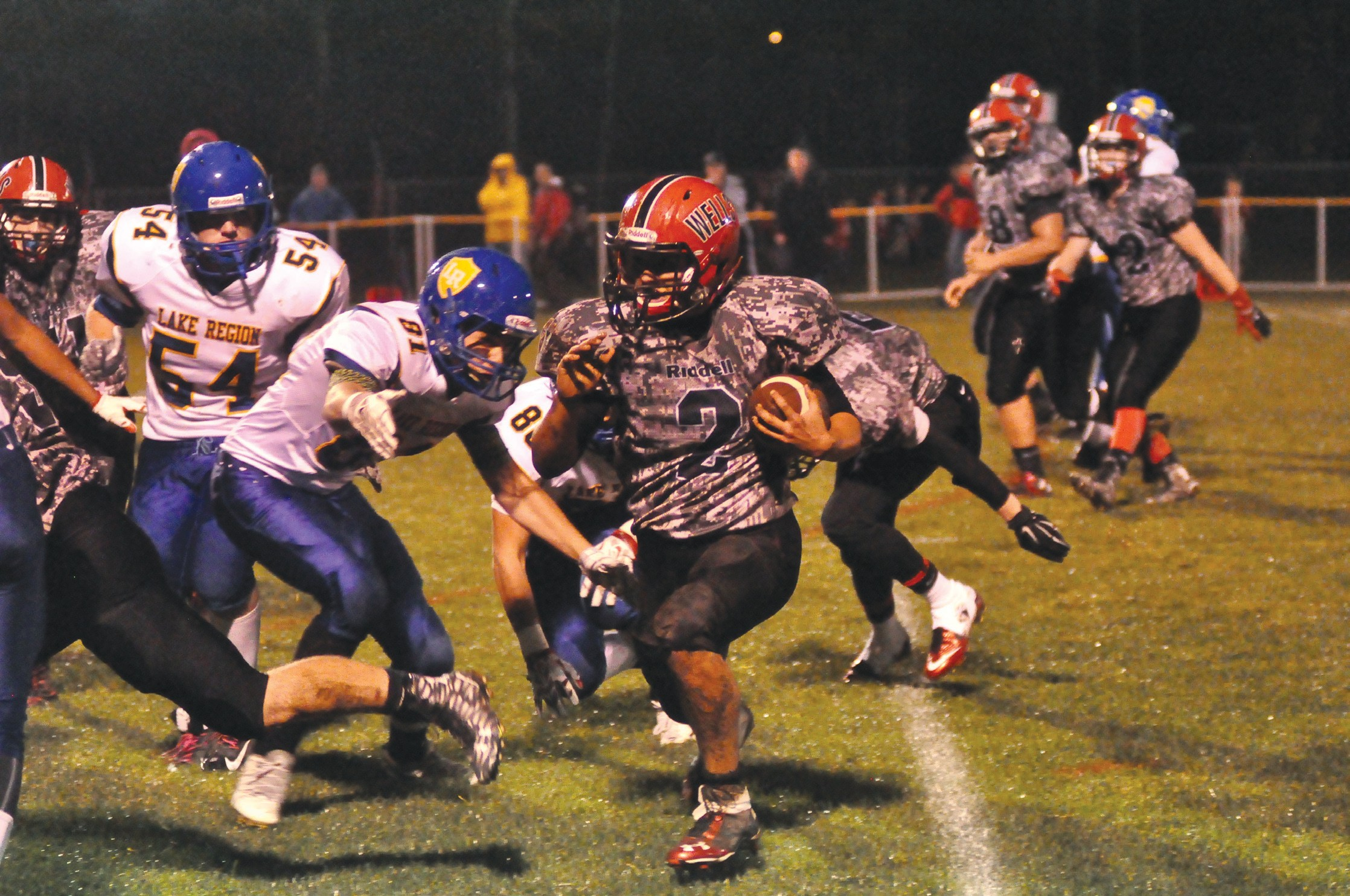 Wells' Nick Hansen (2) runs away from Lake Region defenders Nate Noble (91) and Nick Lepage (88) during the first quarter of the Warriors' 59- 0 victory at Warrior Memorial Field in Wells Friday. Hansen was one of seven different Wells players to score.