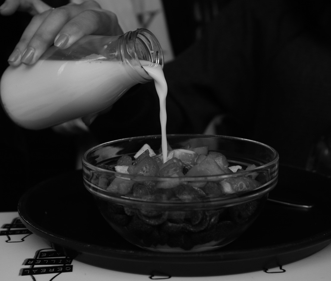 A customer pours organic full cream milk onto her cereal selection that includes chopped strawberries at the Cereal Killer Cafe in Brick Lane, London, Wednesday, Sept. 30, 2015.