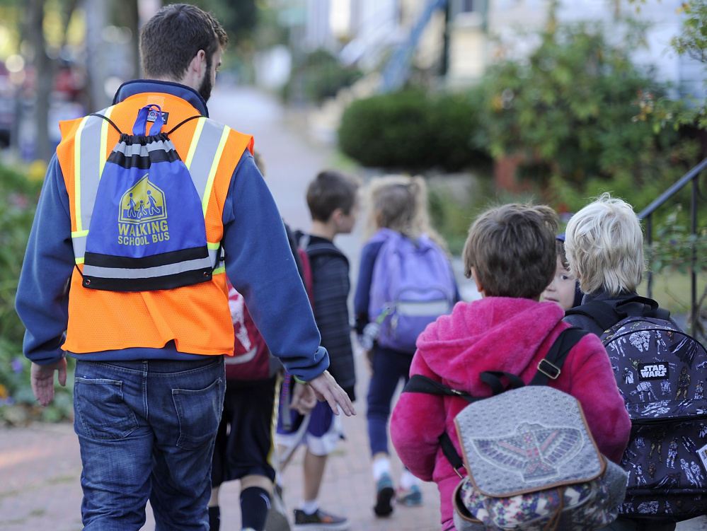 Volunteer Stephen McLeod wears the Walking School Bus backpack as he leads the group to East End Community School.