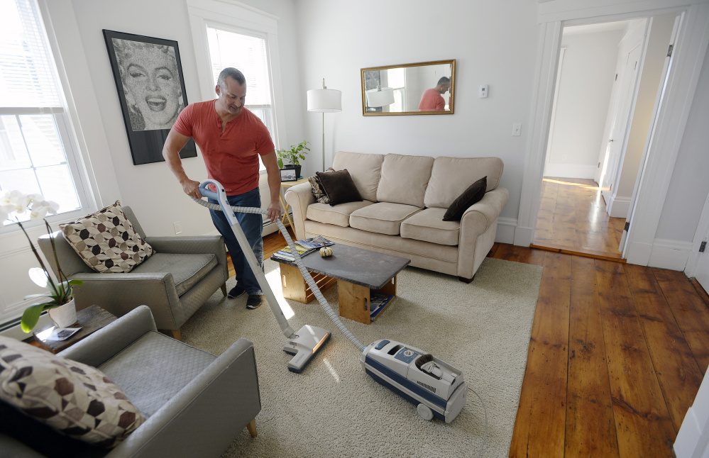 """Gary Wagner vacuums the half of his home he rents out on Airbnb after guests had left Thursday. The West End homeowner started listing the space in July, and says it quickly was booked through October. """"There's a clear demand,"""" he said."""