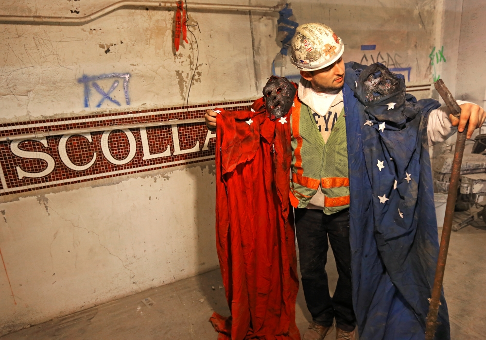 Steve Davis, a bricklayer working on the Blue Line, holds up two tattered rags fastened to bizarre masks at a Boston subway station on Tuesday. The garments were found balled up in a hollow section of concrete that was poured more than 60 years ago.