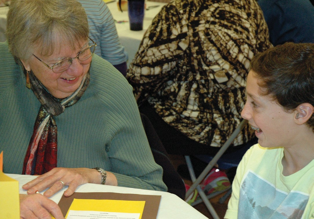 Marty Walton, left, converses with The Middle School of the Kennebunks eighth-grader Keegan MacKenzie during the school's annual Thanksgiving dinner for seniors last Wednesday.