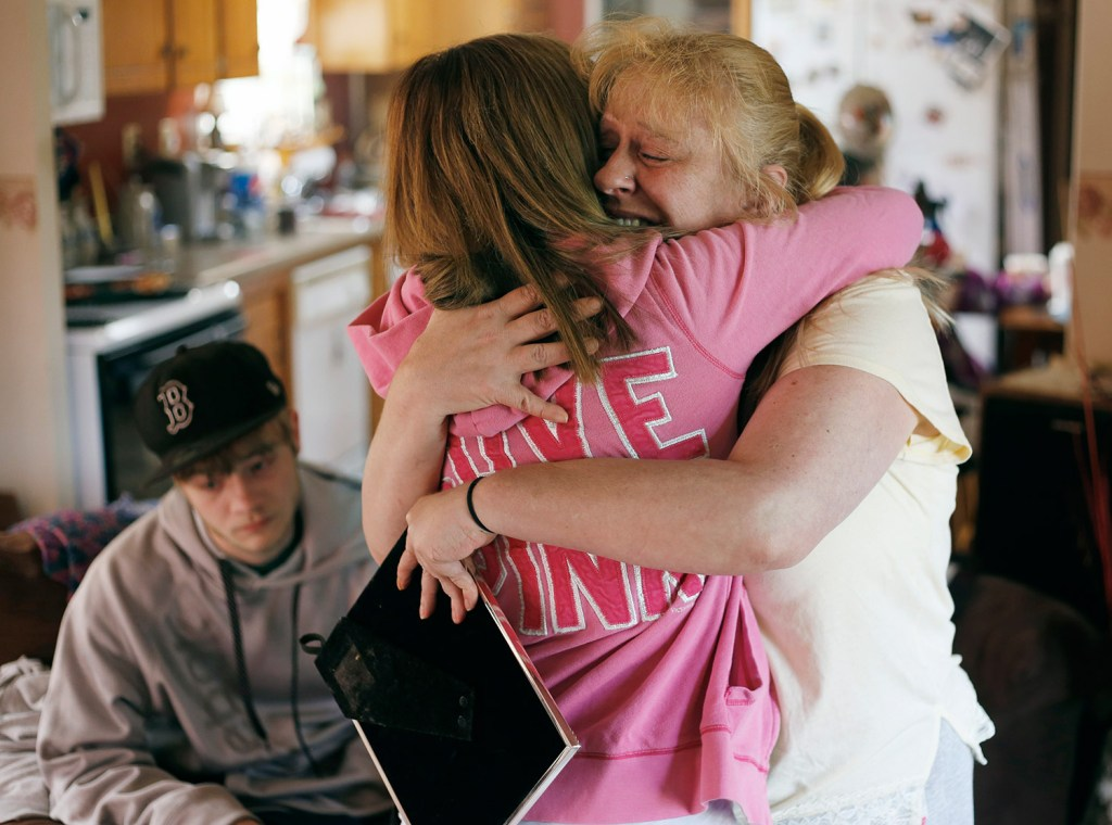 Christa Greene, whose daughter, Angel Greene, was killed in a car crash early Thursday morning, hugs family friend Ansley Moore at her home in Standish. At left, is Angel's boyfriend, Nathan Buzyniski, 19, of Dayton.