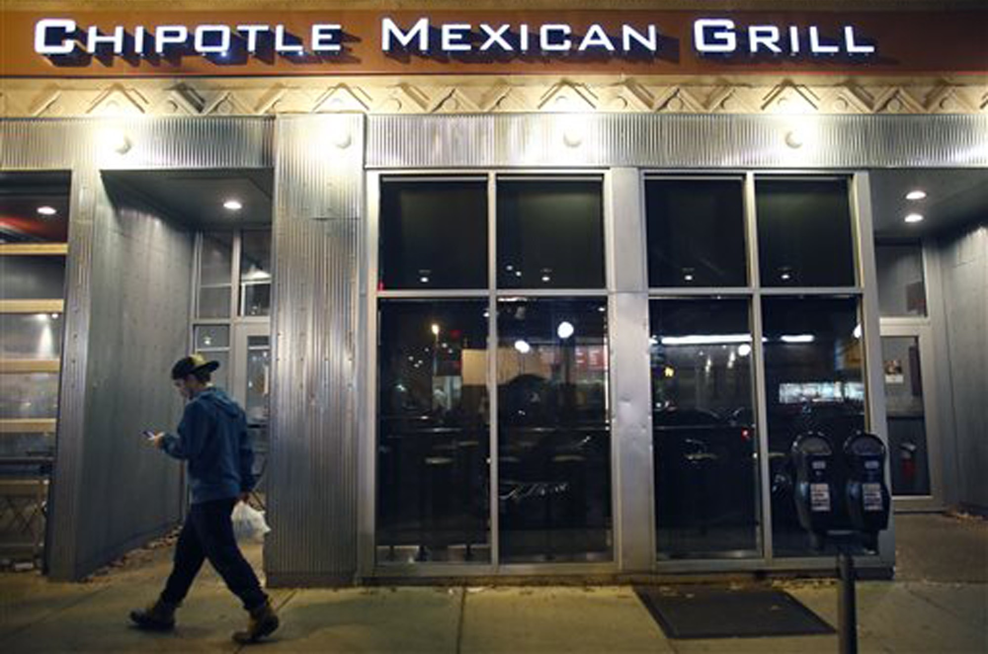 A man walks near a closed Chipotle restaurant on Monday in the Cleveland Circle neighborhood of Boston.