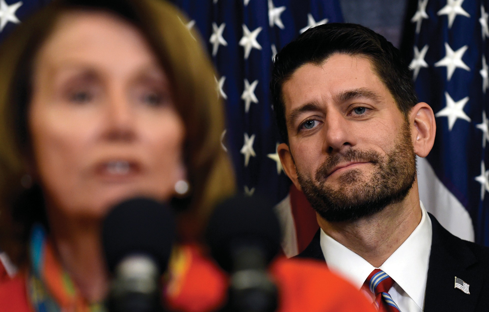House Speaker Paul Ryan of Wis. listens as House Minority Leader Nancy Pelosi of Calif. speaks on Capitol Hill in Washington, D.C. Wednesday.