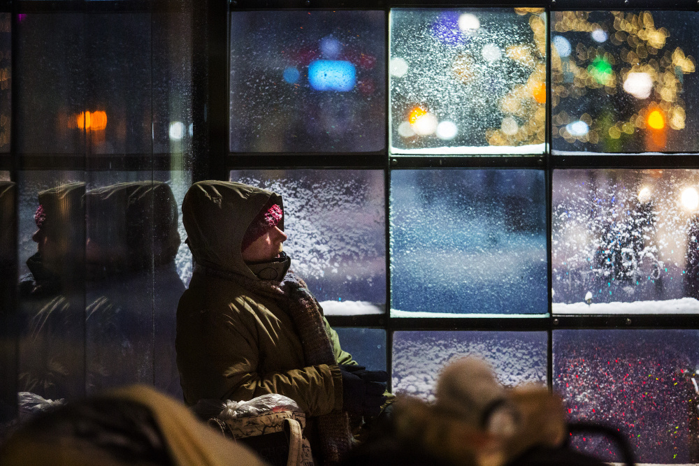 John Horvat, a homeless man in Portland, finds shelter at a Congress Street bus stop as the season's first snowstorm hit southern Maine. More low temperatures and freezing drizzle are likely Wednesday.