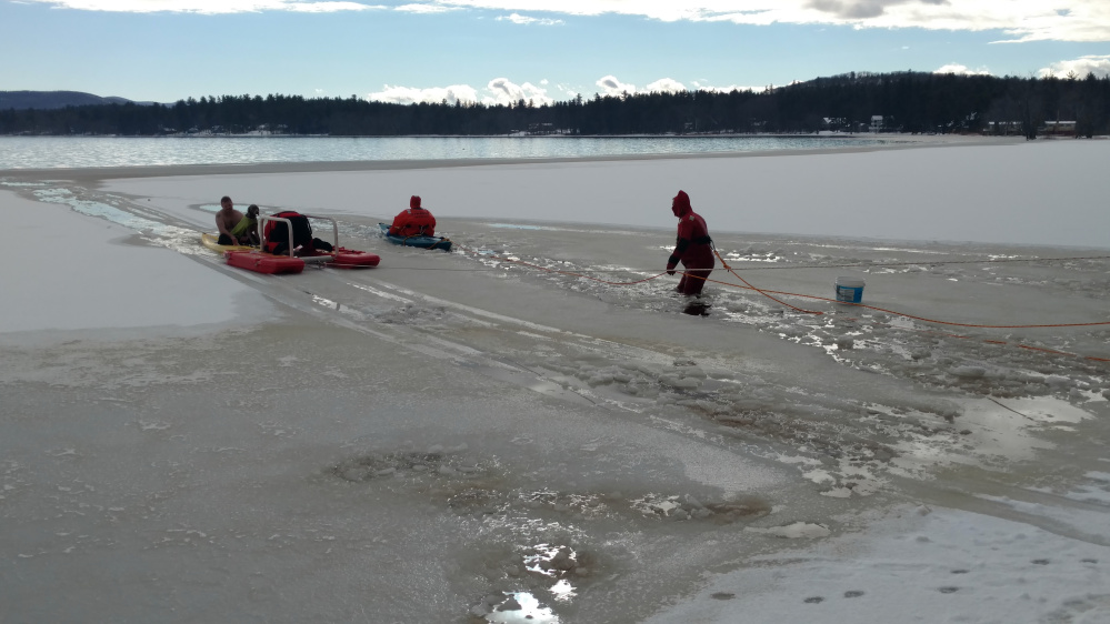 Fryeburg firefighters venture into Lovewell Pond to rescue a dog and a man on Thursday.