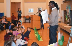"EDUCATOR AND CHILDREN'S AUTHOR Rohan Henry reads his new book, ""The Perfect Garden,"" to children at Bowdoin College at Monday's Martin Luther King Day event."