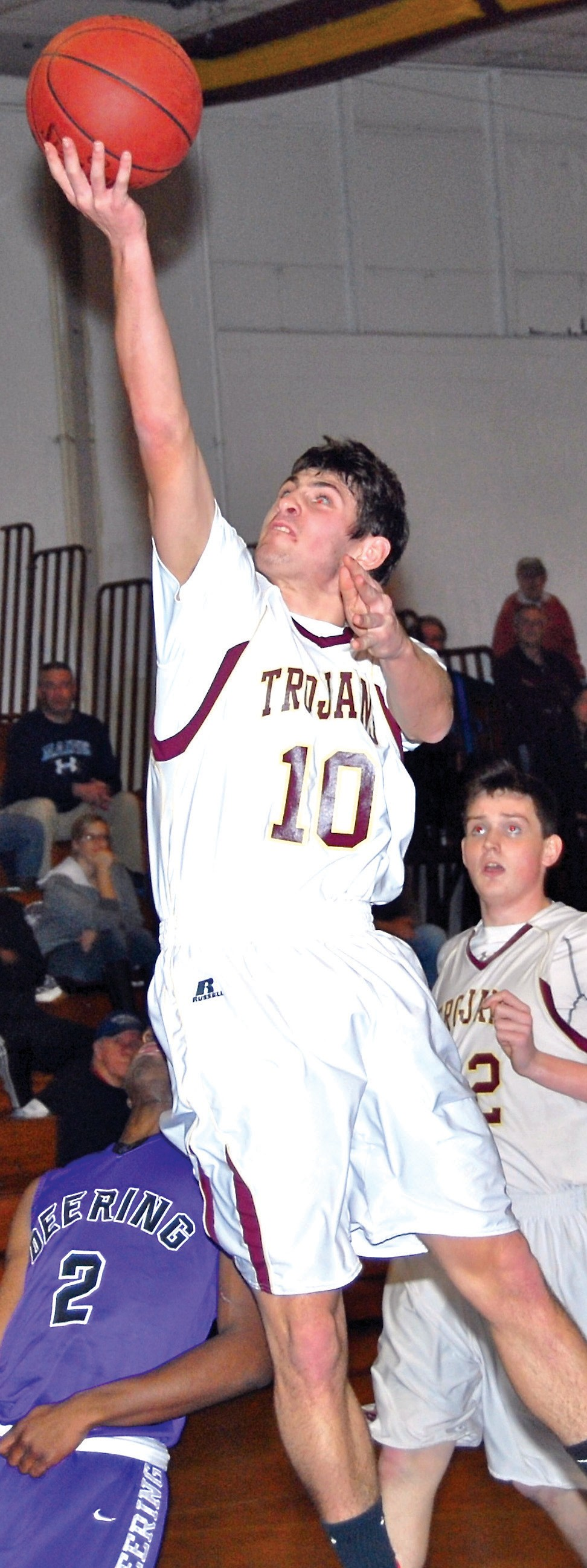 Above: Thornton Academy's Ben Lambert flies to the basket for a layup during Tuesday night's game against Deering. Left: TA's Corey Hart gets a shot off over Deering's Jean Claude Butera in the second half on Tuesday night.