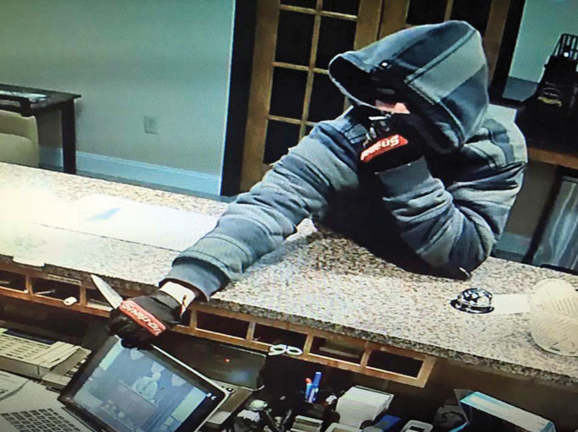 This still image from video surveillance, posted on the Sanford Police Department's Facebook page, shows a man attempting to rob the Super 8 Motel in Sanford Nov. 24. While Facebook has proven invaluable to police departments in York County in identifying those wanted in connection with various crimes, so far, no one has been charged in this case.