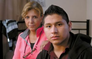 MARVIN VELASCO, 15, right, poses for a photo with his new sponsor, Ingrid Ainspac, at their home in Los Angeles on Jan. 11. After escaping from a previous sponsor who was abusive, he sought sanctuary in a nearby church, where he met a parishioner who took him in and became his legal guardian. He now lives with a Guatemalan immigrant family, which is raising him as a son.