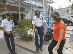 SECURITY GUARDS use metal detectors to check a visitor's bag outside a shopping mall near the Starbucks cafe where Thursday's attack occurred in Jakarta, Indonesia, Friday. Indonesians were shaken but refusing to be cowed a day after a deadly attack in a busy district of central Jakarta that has been claimed by the Islamic State group.