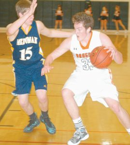 BRUNSWICK FORWARD CORBAN TEEL drives down the baseline past Medomak Valley defender Kyle Donlin (15) during a boys high school basektball game at Brunswick on Thursday. The Dragons fell, 67-61.