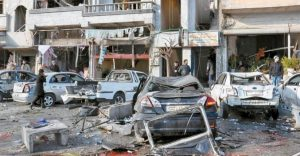 SYRIAN CITIZENS gather at the scene where twin bombs exploded at a government-run security checkpoint, at the neighborhood of Zahraa, in Homs province, Syria, today.