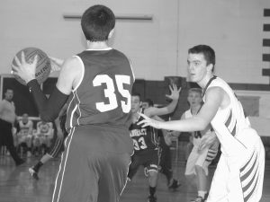 RICHMOND HOSTED Rangeley in an East-West Conference boys basketball game on Tuesday, with the Bobcats coming out on top, 68-50. Above, Richmond's Matt Holt, right, defends Rangeley's Ricky Thompson (35), while to the right, Bobcat guard Tyler Soucy (22) looks for room against a Lakers defender.