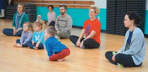 A GROUP OF PARENTS and young children attend a preschool yoga class at a Bath Area Family YMCA open house event at Brunswick Landing on Saturday. The organization will officially open its new Landing location to the public on Tuesday.