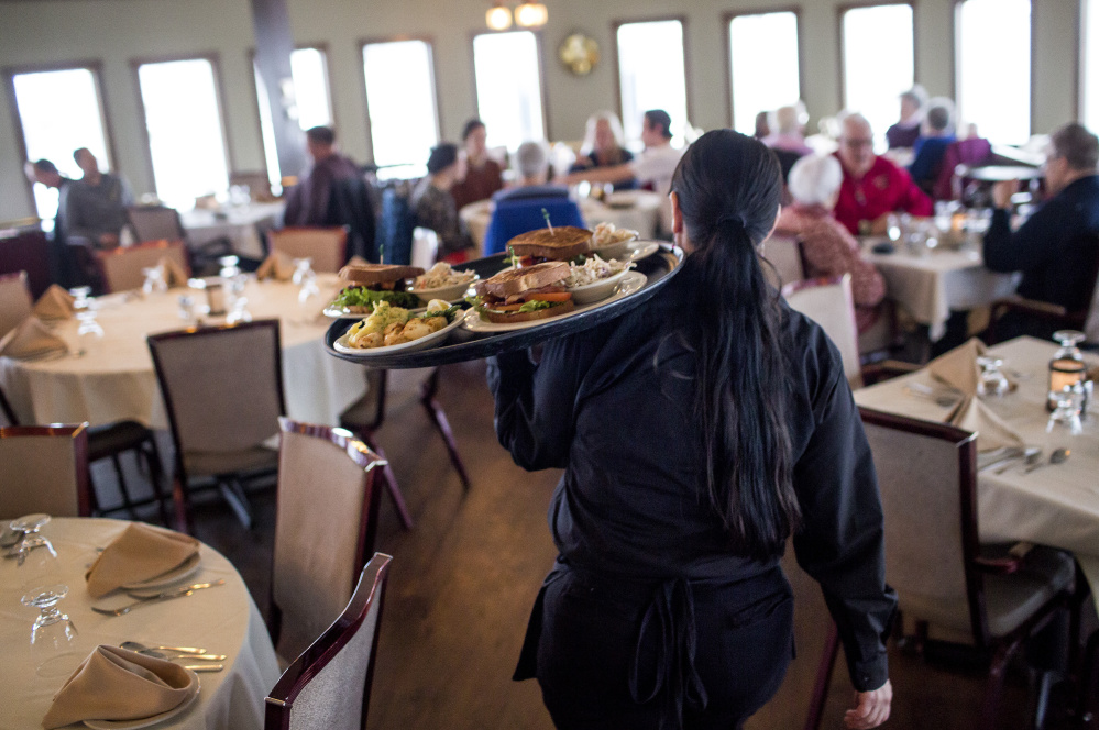 "Dawn Murray, a server at DiMillo's On the Water, carries food to waiting customers during the lunch rush Friday at the Portland restaurant. Her employer, Steve DiMillo, says, ""It's time for someone to make a call (about the legality of Portland's wage ordinance), so they don't leave operators or the wait staff not knowing what their pay should be."""