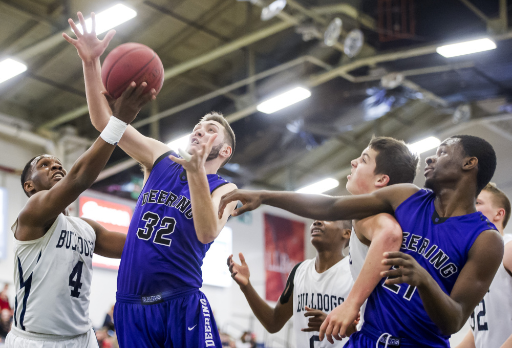 Amir Moss of Portland, left, tries to lay the ball up while pressured by James Sinclair of Deering during the first half of their SMAA game Friday night at the Portland Expo. Looking on are Terion Moss, center, and Joe Esposito of Portland, and Ben Williams of Deering. Gabe Souza/Staff Photographer