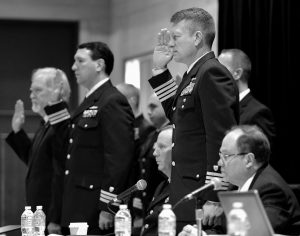CAPT. JASON NEUBAUER, right, and the board is sworn in at the beginning of the hearings into the sinking of the El Faro ship in Jacksonville, Fla., Tuesday. The series of U.S. Coast Guard hearings will seek answers about why freighter El Faro sank near the Bahamas last fall, killing all crew members in the worst U.S. commercial maritime disaster in decades.