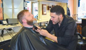ADRIAN REYES WORKS ON Jeremie Buck of Topsham. Reyes provides a full range of services, including specialty cuts, fades and beard grooming.