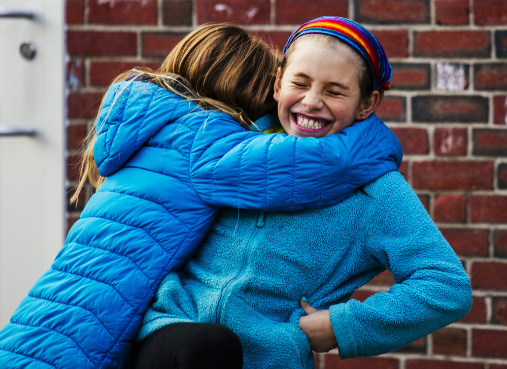 """Lucy Tidd, right, is embraced by a classmate after playing a round of four square during recess at Lyseth Elementary School in Portland on Jan. 27. Fellow students have been """"very accepting,"""" Principal Lenore Williams said."""