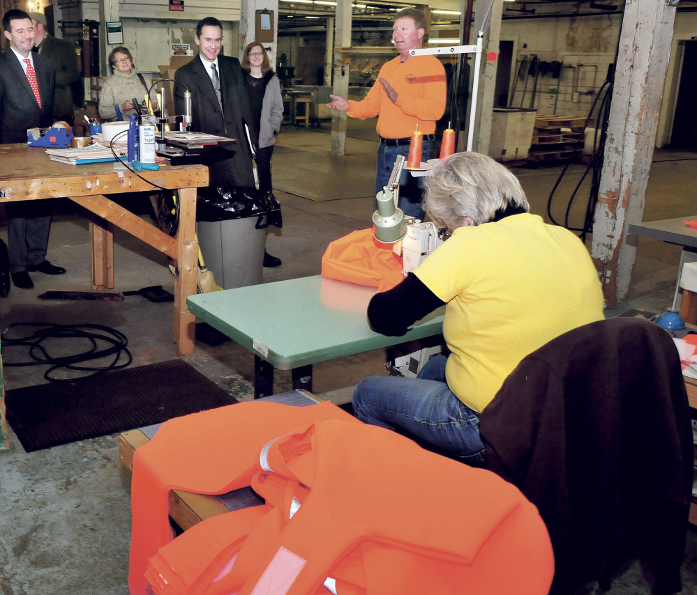 A chance meeting in the lobby of Wal-Mart's headquarters with CEO Greg Foran resulted in an order for 800 tick-repellent dog vests from Skowhegan's Dog Not Gone Visibility Products. Owners Julie and Bill Swain, center, seized on the opportunity to tell Foran of their innovative dog vests last summer. On Wednesday, the first order shipped out to Wal-Mart stores across the country. David Leaming/Morning Sentinel