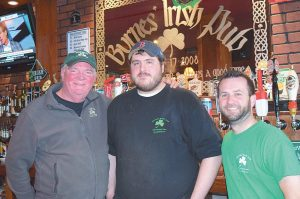 FROM LEFT, Joe Byrnes, owner of Byrnes' Irish Pub, Brian Lindall and Nate Colby get ready for St. Patrick's Day. After flooding and extensive repairs over the last month, the Irish pub located at Brunswick Station is ready to celebrate. See story, page A2.