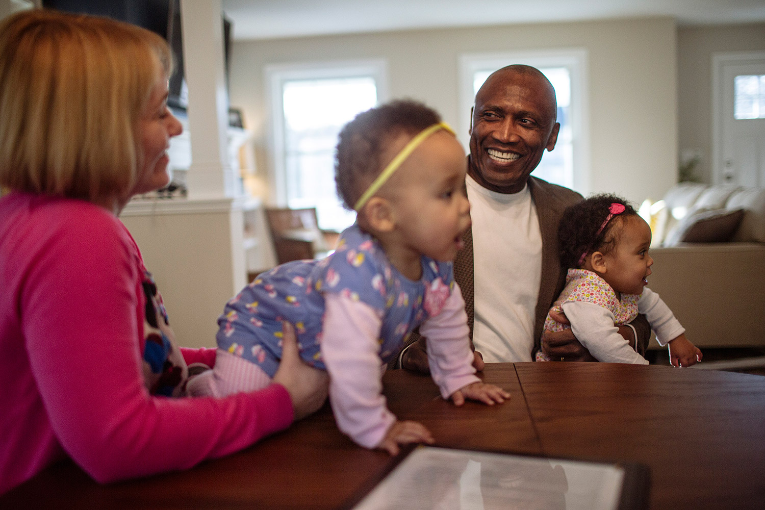 John Estrada smiles at his  wife, Elizabeth Cote Estrada, with daughters Eva and Marie at their home in Freeport. Whitney Hayward/Staff Photographer