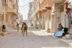 SYRIAN GOVERNMENT SOLDIERS patrol a street in the ancient city of Palmyra, central Syria, in this photo released on Sunday by the Syrian official news agency SANA. The amount of destruction found inside the archaeological area in the historic town was similar to what experts have expected but the shock came Monday from inside the local museum.