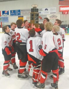 THE BRUNSWICK JUNIOR HIGH SCHOOL hockey team gathers to hoist the Mariner Cup after winning the Hawkins Division championship during play in the Southern Maine Middle School Hockey League. Brunswick defeated South Portland, 5-4, in the title game.