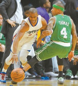 LOS ANGELES CLIPPERS guard Chris Paul, center, drives past Boston Celtics guard Isaiah Thomas, right, during the first half of an NBA basketball game on Monday in Los Angeles.
