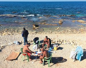 "LEBANESE MEN PLAY CARDS and smoke water pipe as they sunbath during unusually warm weather last month along the Mediterranean Sea in Beirut, Lebanon. Earth got so hot last month that federal scientists struggled to find words, describing temperatures as ""astronomical,"" ""staggering"" and ""strange."""