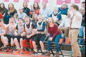 LISBON UNIFIED Basketball team student athlete coaches Jonah Sautter, right and his sister Bree, second from right, cheer a three-point play during Tuesday's game against Deering/Portland.