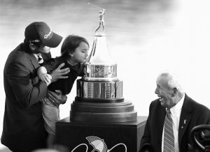 ARNOLD PALMER, right, smiles as he watches Jason Day, of Australia, hoist his son Dash up to kiss the championship trophy after Day won the Arnold Palmer Invitational golf tournament in Orlando, Fla., on Sunday.