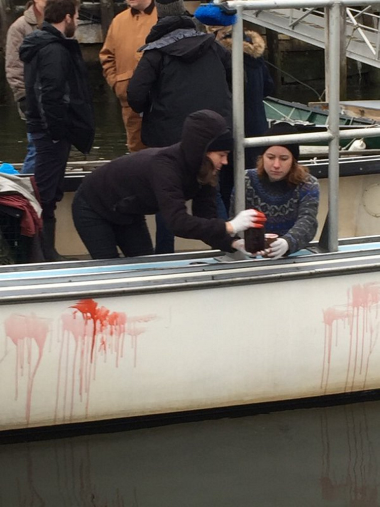 """Crew members of the horror film """"Island Zero"""" apply fake blood to a lobster boat in Camden Harbor last week."""