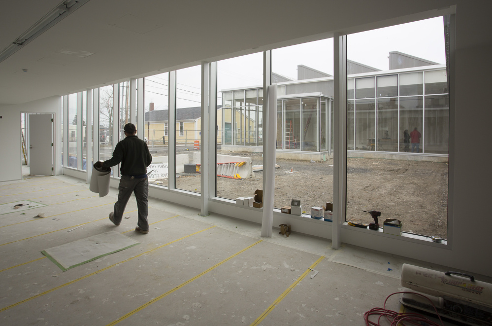 Workers at the new Center for Maine Contemporary Art building in downtown Rockland. The center is scheduled to open in June. Below: One of the architecturally unique spaces in the gallery.