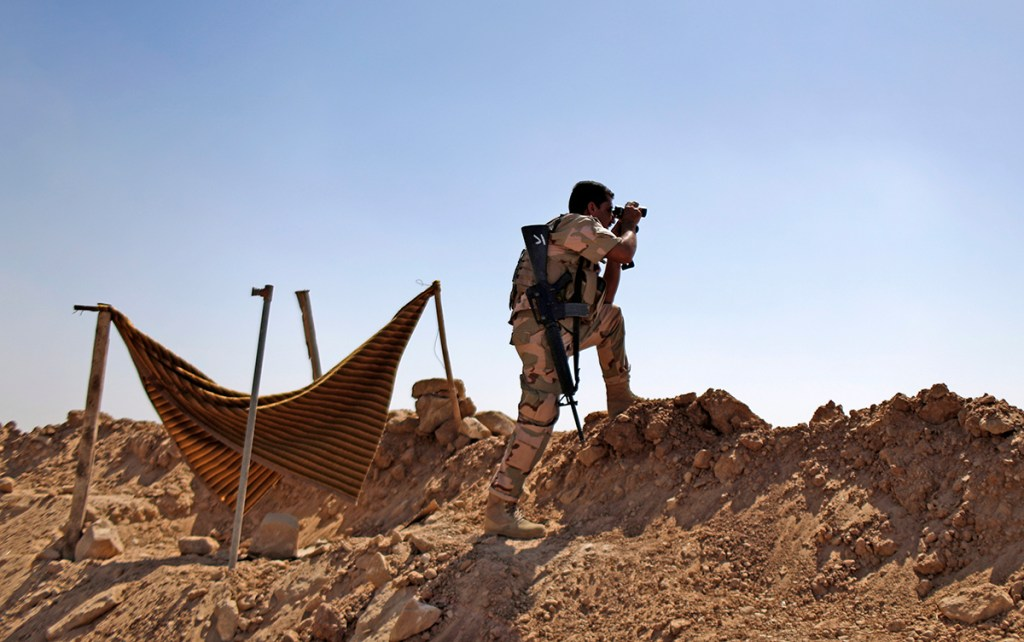 A Kurdish Peshmerga fighter checks on Islamic State group's positions on the outskirts of Makhmour, about 180 miles north of Baghdad, in this September 2014 photo. Although Kurdish forces have pushed the militants out, Makhmour still has the feel of a warzone, and many residents have stayed away. The Associated Press