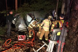 Firefighters work to free a woman trapped in a car after crashing into trees in the median of Interstate 295 northbound in Richmond Thursday night. DARCIE MOORE/THE TIMES RECORD