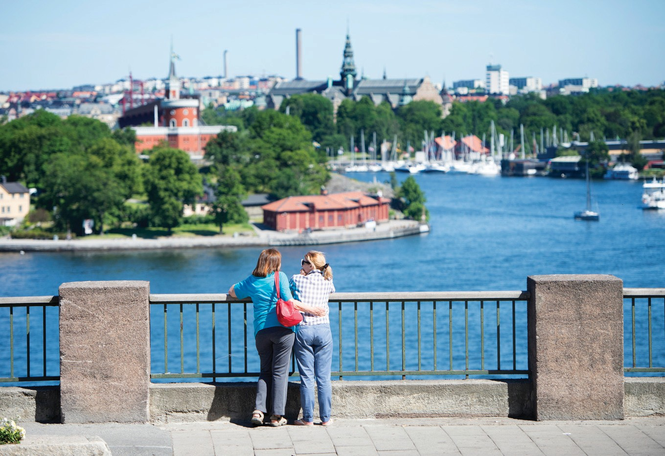 "In this July 2, 2015, file photo, tourists look at a view of Stockholm. The Swedish Tourism Association has set up a hotline that lets callers worldwide ""get connected to a random Swede."""