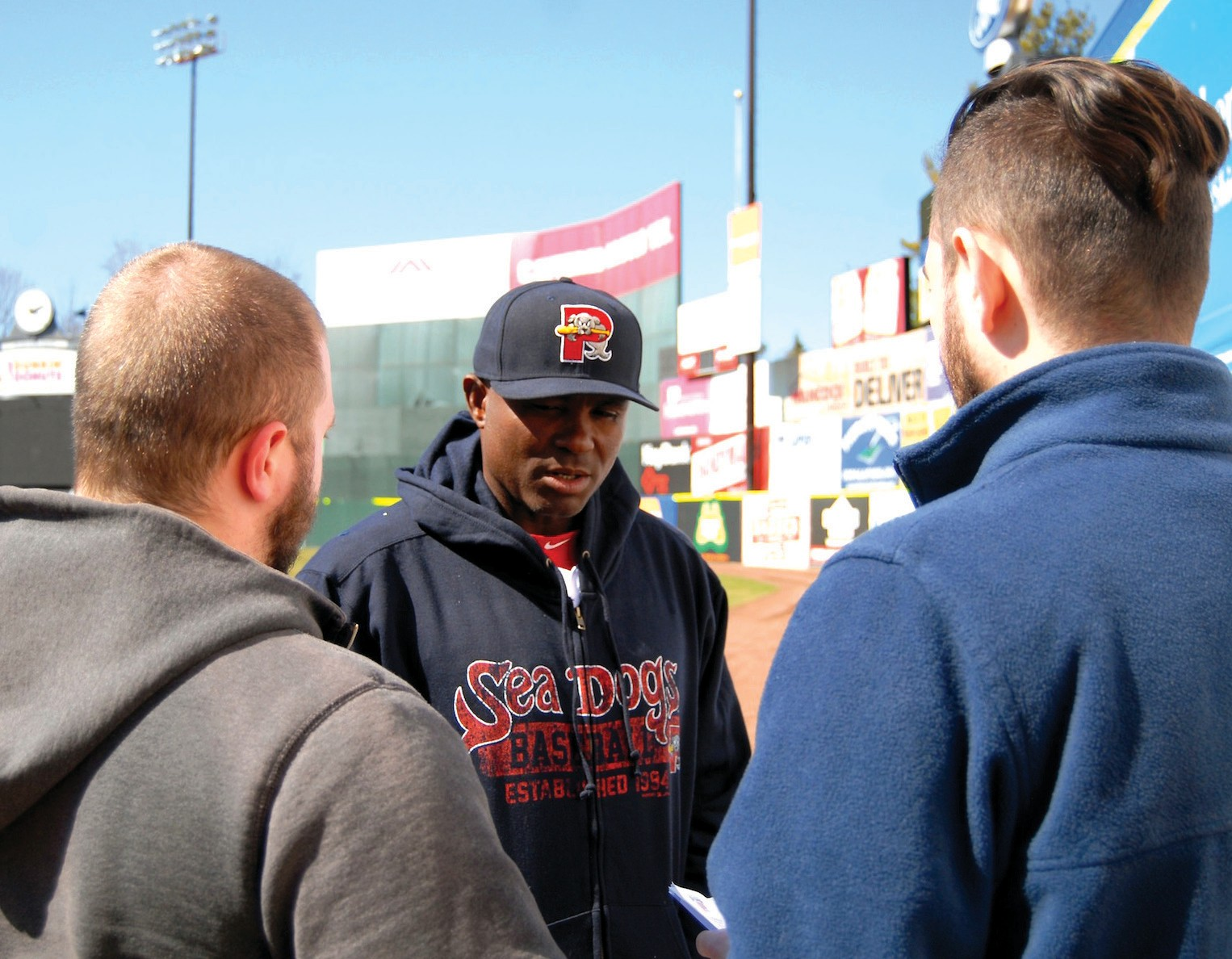 Portland Sea Dogs manager Carlos Febles (center) talks with Alex Sponseller (left) of the Journal Tribune and Christian Sandler (right) of the Brunswick Times Record during Media Day on Tuesday at Hadlock Field.