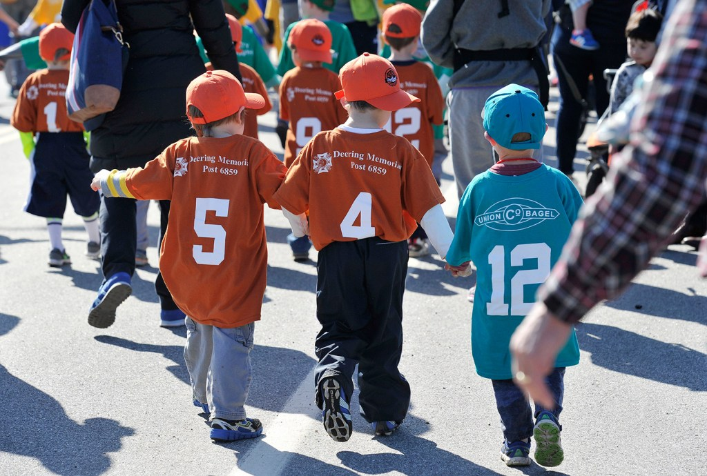 Young Little Leaguers march in the parade during Opening Day ceremonies in Portland on Saturday.