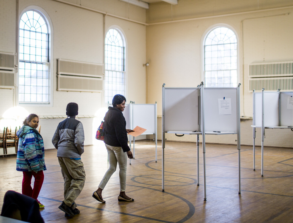 Angelina Wani, 9, and her brother Remijo, 11, follow their mother Betty Lasu into the Woodfords Congregational Church on Tuesday while she votes on a referendum to pay for renovations at Hall School.