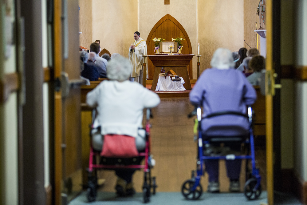 Rev. Paul Dumais steps away from the altar after celebrating Holy Thursday Mass at the d'Youville Pavillion at St. Mary's Hospital in Lewiston.